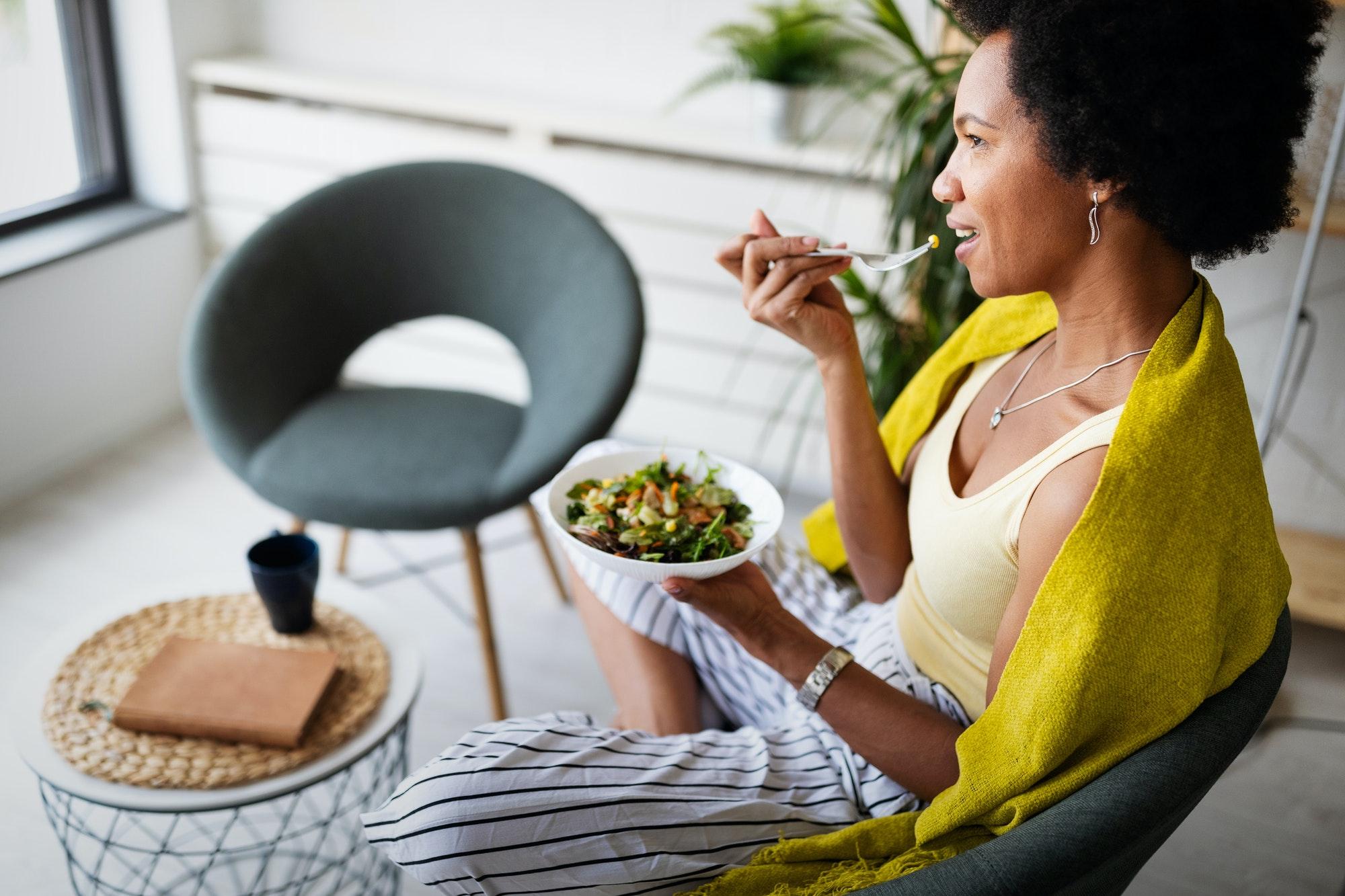 Beautiful woman eating healthy fresh organic salad