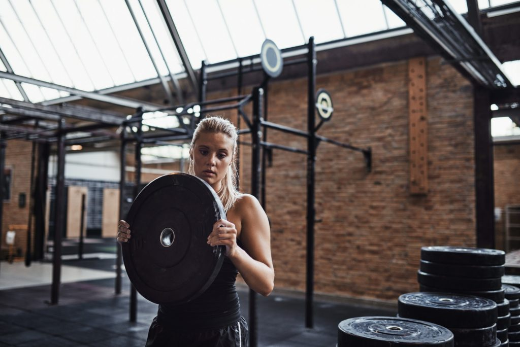 Fit young woman selecting weights for a gym workout