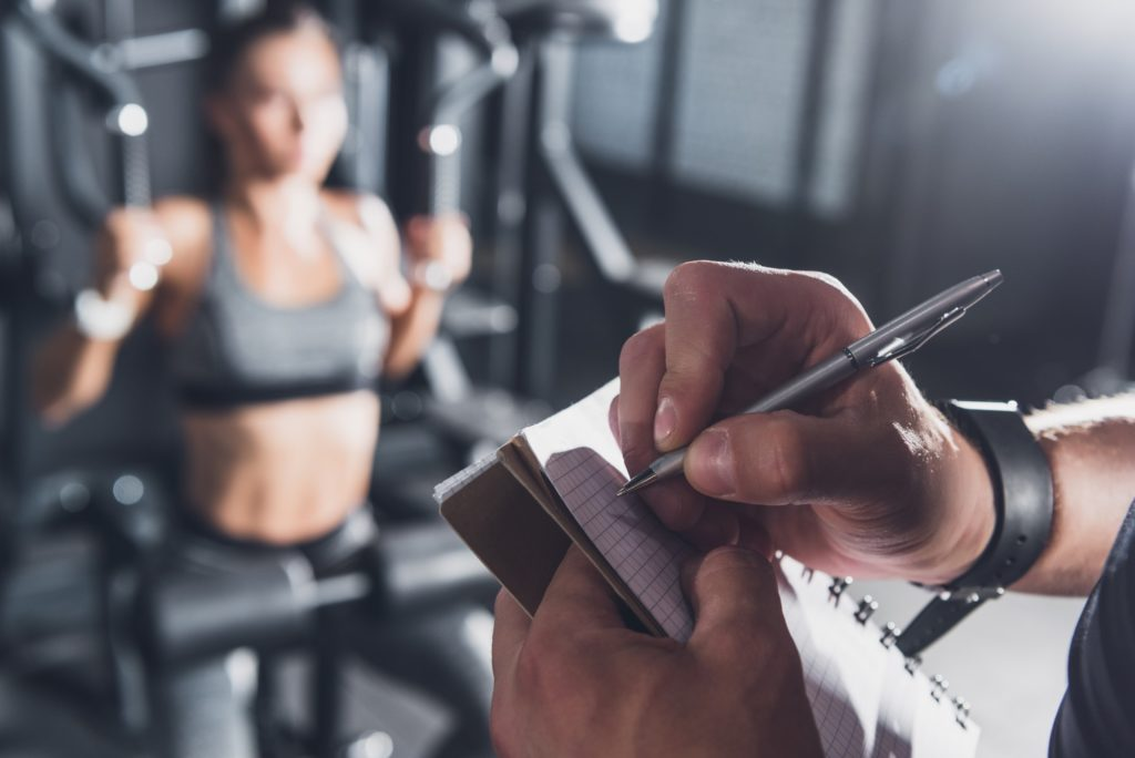 close up view of trainer writing in notebook while woman working out in gym