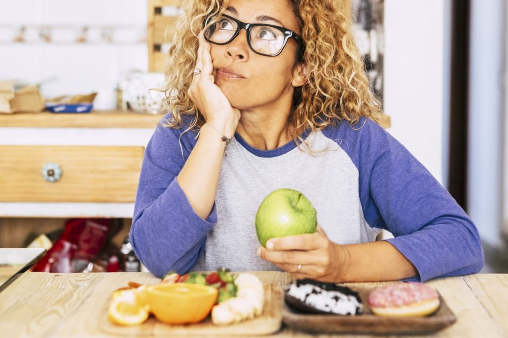 woman chooise apple or donut - diet and good nutrition lifestyle, fruit and donut