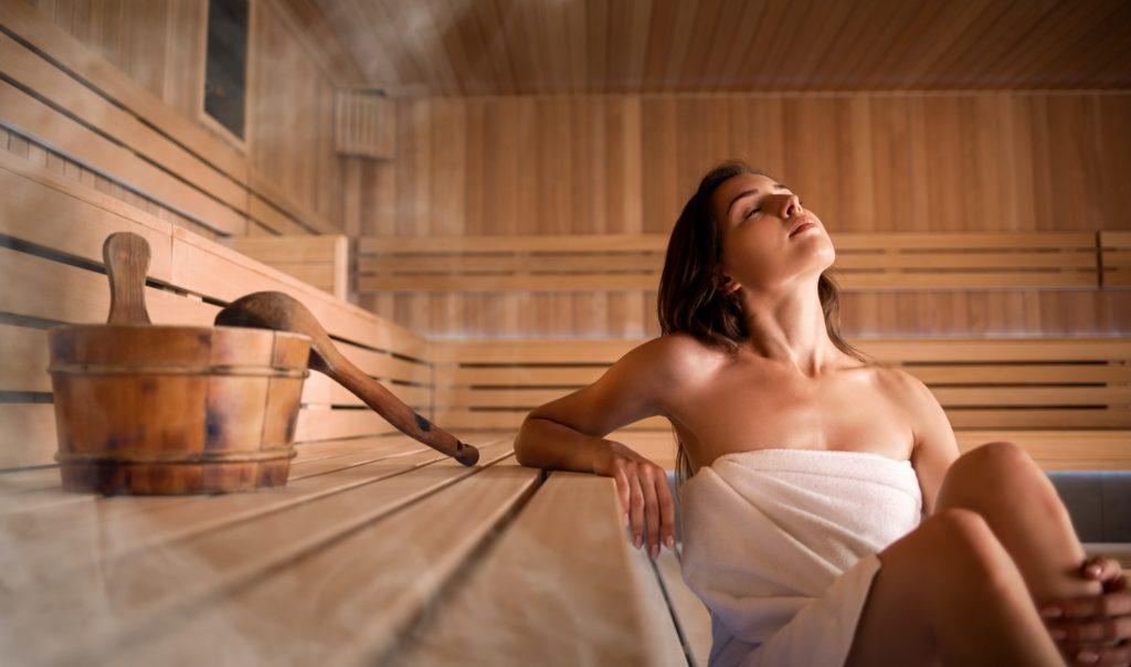 Beautiful young woman relaxing in Finnish sauna