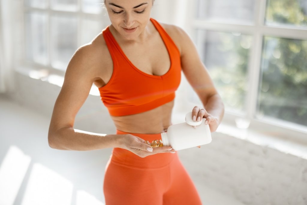 Sports woman takes supplements or vitamins at gym